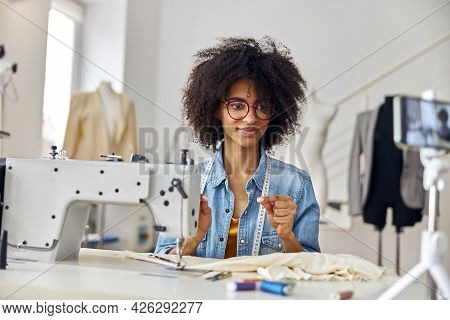 African-american Dressmaker Holds Thread Shooting Video At Workplace In Spacious Studio
