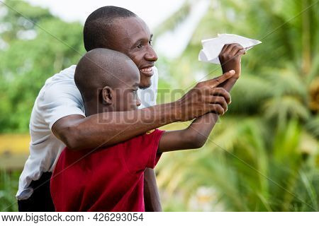 Little Boy In Red T-shirt Standing Near His Father Playing With A Paper In The Shape Of Airplane Smi