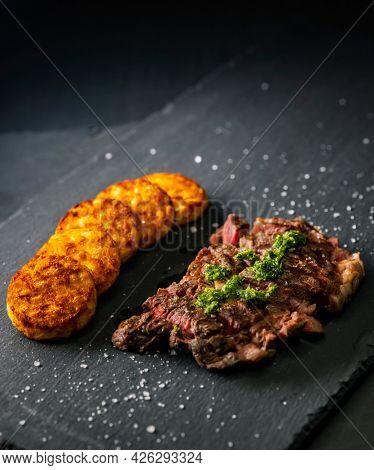 beef steak with potato patties on a dark background