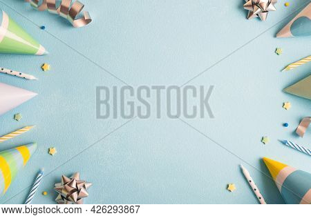 Birthday Party Background. Carnival Caps, Confetti, Streamers And Candles On Pastel Blue Surface. To