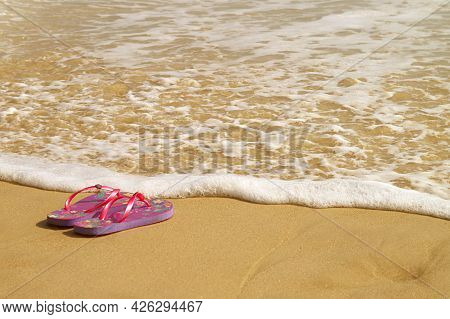 Sea Foam Splashing On The Beach A Pair Of Sandals