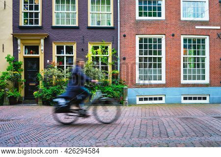 Motion blurred bicycle rider cyclist man on bicycle very popular means of transport in Netherlands in street with old houses of Delft, Netherlands