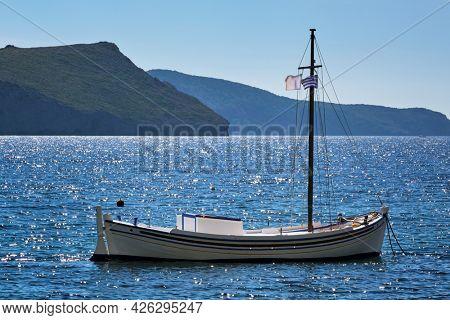 Traditional greek fishing boat in the Aegean sea with greek flag, Milos island, Greece