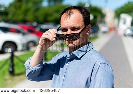 Caucasian Man Forty Years Old Businessman On The Street Takes Off His Sunglasses.
