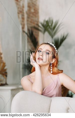 Portrait Of A Red-haired And Pale-skinned Woman In A Silk Dress With Makeup Made Of Pearls On Her Ha