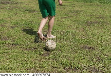 Barefoot Amateur Soccer Player Doing Trick  With Heel And Shabby Ball On Bad Lawn