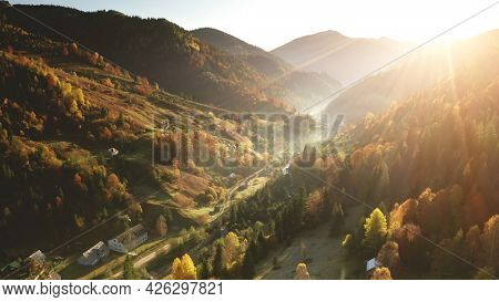 Aerial mist over mountain village at sun day. Autumn nobody nature landscape. Cottages on mount hills. Green pine trees forest at rural road in fog. Unknown misty Carpathian ridges, Ukraine, Europe