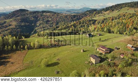 Village at green mountain top aerial. Nobody nature landscape. cottages with rural ways. Cinematic autumn greenery trees, grass. Carpathians mount ranges, Ukraine, Europe. Travel and tourism concept
