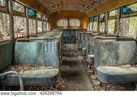 Inside View Closeup Of A Abandoned Old Vintage School Bus With Seats And Broken Windows And A Rottin