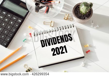 Notepad With Inscriptions Dividends 2021 On A White Office Background.