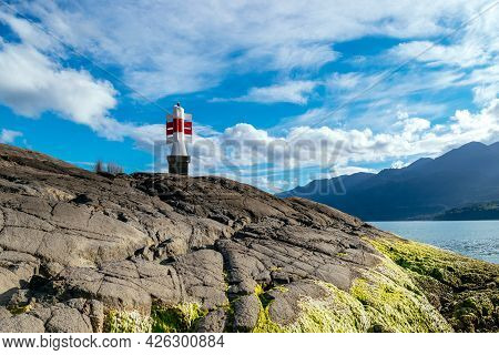 The Harbor Ramp Leads To A Lighthouse On A Small Island In Cochamo, Chile.