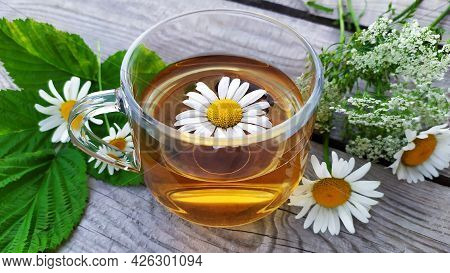Chamomile Tea. Flowers, Leaves And A Cup With Tea On A Wooden Background. Drink With Chamomile Flowe
