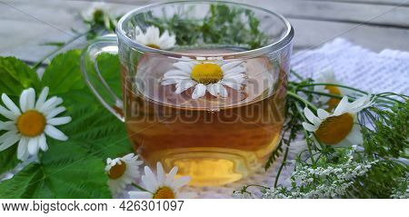 Chamomile Tea. Flowers, Leaves And A Cup With Tea On A Wooden Background. Drink With Medicinal Chamo