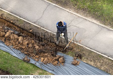 Migrant Labor. A Worker Digging A Ditch And Pulling An Armature.