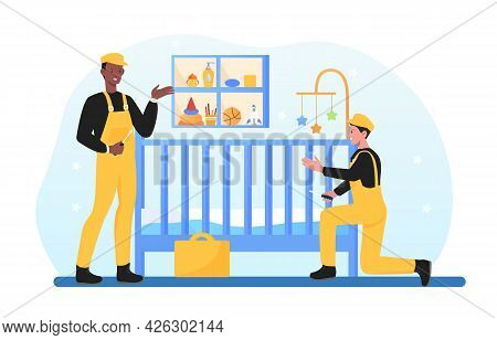 Young Smiling Handymen Are Installing Child Cot In Bedroom. Two Men In Overalls Are Assembling Child