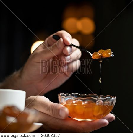 Apricot Jam, Fruit Or Berry Confiture. Male Hands Hold Spoon And Glass Bowl Of Jam On Black Backgrou