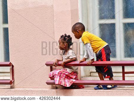Paris France - June 21 2009; Two Black Children On Window Ledge Exterior Of Building Side View Looki