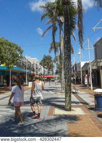 Tauranga New Zealand- November 24 2015;  Young Couple Walking Across Red Square In City Business Dis
