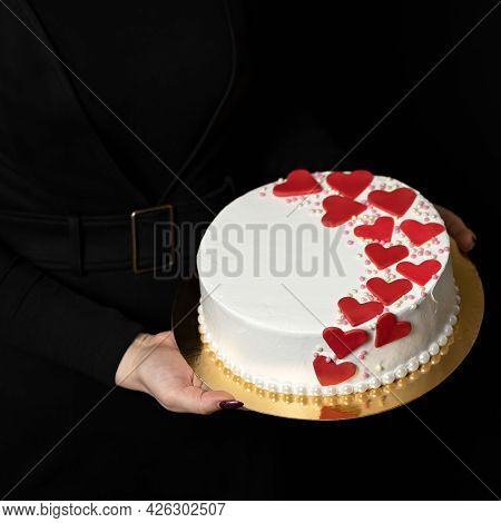 Woman Holds Festive Cake On Black Background. White Round Iced Dessert Decorated With Many Red Heart