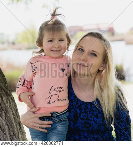 A Young Beautiful Woman In A Blue Dress And A Little Toddler Girl Are Sitting On A Park Bench. Happy