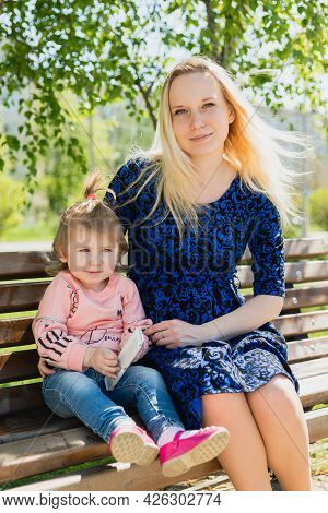 A Young Beautiful Pregnant Woman In A Blue Dress And A Little Toddler Girl Are Sitting On A Park Ben