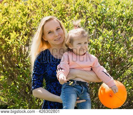 A Young Beautiful Mother Holds Her Toddler Daughter In Her Arms In Nature On A Sunny Day. The Happin