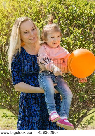A Young Beautiful Mother Holds Her Toddler Daughter In Jeans In Nature On A Sunny Day. The Happiness