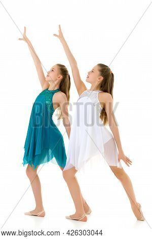 Pretty Girls Dancers Dancing Synchronously In Studio, Two Beautiful Twin Sisters Wearing White And B