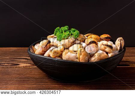Frozen Shellfish Meat With Green Parsley In A Clay Black Bowl On Wooden Table.