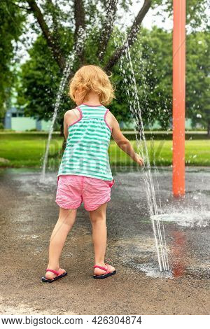 Little Child Playing At Water Splash Pad Fountain In Park Playground On Hot Summer Day.