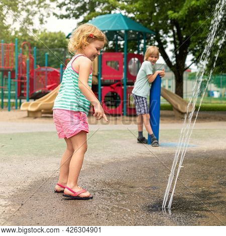 Little Happy Children Playing At Water Splash Pad Fountain In Park Playground On Hot Summer Day.