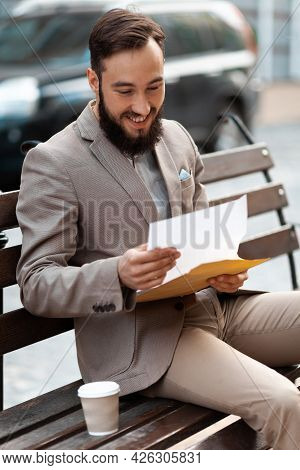 A Bearded Man Reads A Positive Judgment On A Bench. Student Scholarship, Approved Visa Documents.