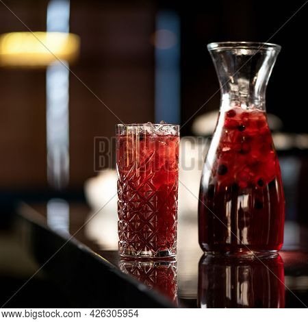 Glassware With Red Berries And Mint Lemonade Drink On Backlit Blurred Background. Healthy Fresh Juic