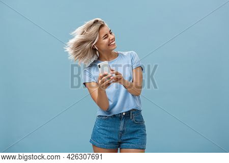 Great Vibes Carrying Me Away. Carefree Joyful Attractive Young Blonde Female In Stylish Outfit Wavin