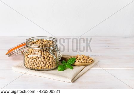 Raw Chickpea Beans In A Clip Top Glass Jar And In A Large Wooden Spoon On A White Rustic Table. Dry