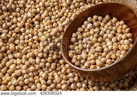 Raw Chickpeas In A Wooden Bowl In A Bag Of Chickpea Beans. Legume Dietary Fibers And Vegetable Prote