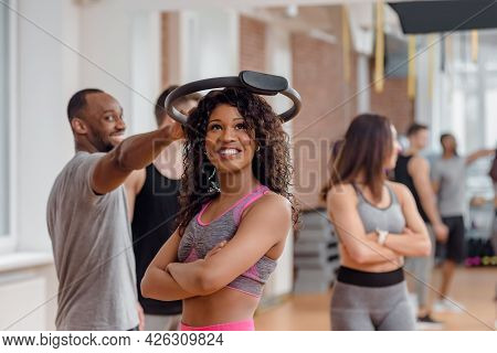 Group Of Happy Multinational People Exercising In Gym Using Resistance Ring