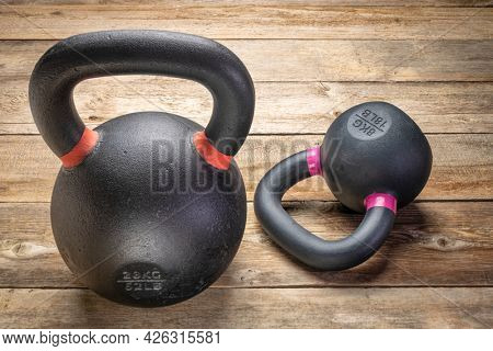 two heavy iron kettlebells on a rustic wood background, weight training and  fitness concept