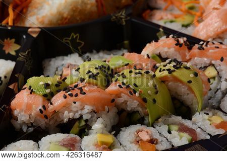 Set Of Sushi Rolls  On A Black Plastic Platter Decorated With Soy Sauce And Spices. Ready For Delive