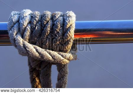 Closeup of rope knot tied to railing.