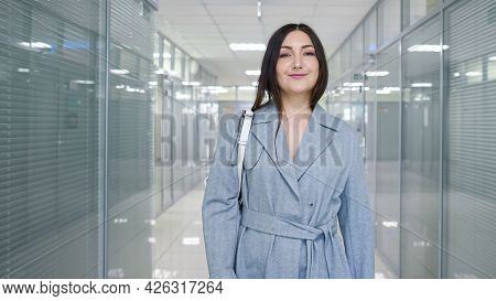 Young Woman With Long Loose Hair Walks Along Hallway With Transparent Glass Office Doors And Bright