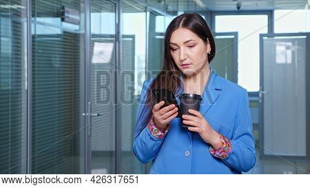 Concentrated Brunette In Blue Jacket Types On Black Smartphone And Holds Coffee Cup Standing In Hall