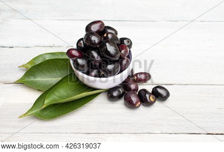 Jamun Or Black Plum In A Bowl With Leaves Isolated On White Wooden  Background With Copy Space, Also