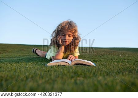 Cute Child Boy Reading Book Outdoor On Green Grass Field. Smart Child Reading Book, Laying On Grass