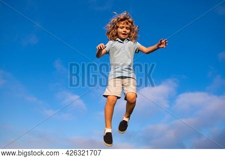 Caucasian Boy In A Park Running And Smiling On Blue Sky. Happy Kid Laughing. Emotion Face Joy Child.