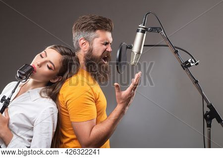 Couple Singing. Coupl In Recording Studio. Music Performance Vocal. Singer Singing Song With A Micro