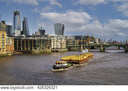 A Tug Pulling A Container Barge Up The River Thames. With The Southwark Bridge In The Background.