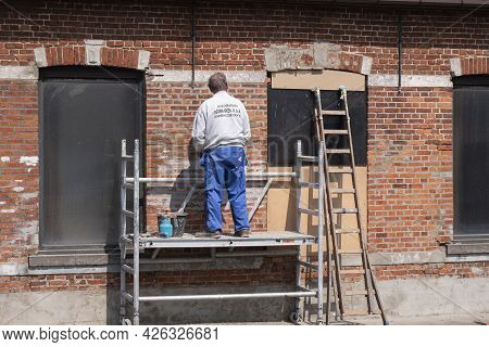 Sint Gillis Waas, Belgium, April 21, 2021, Painter Stands On A Scaffold And Inspects An Old Stone Wa