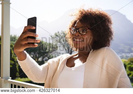 Smiling african american woman on sunny balcony of country home taking selfie with smartphone. spending free time at home.
