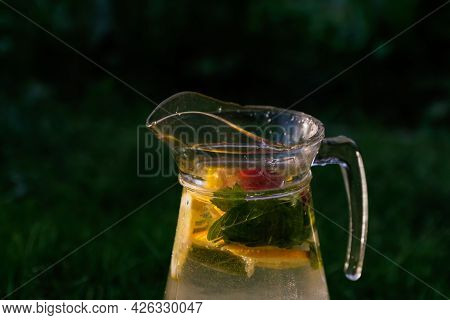 Defocus Glass Jug Of Lemonade With Slice Lemon And Mint On Natural Green Background With Water Drops